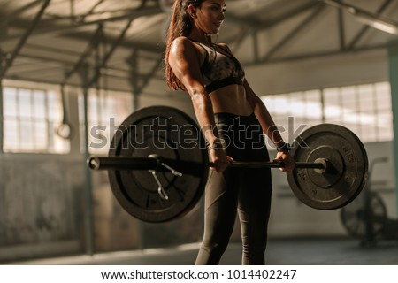 Determined and strong fitness woman training with heavy weights in fitness club. Female athlete holding heavy weight barbell in gym. #1014402247