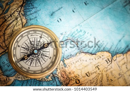 Old vintage retro compass on ancient map background. Travel geography navigation concept background. #1014403549