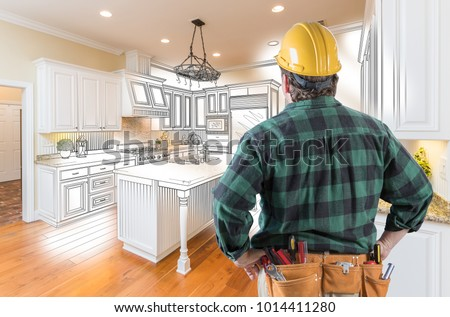 Male Contractor with Hard Hat and Tool Belt Looking At Custom Kitchen Drawing Photo Combination On White. Royalty-Free Stock Photo #1014411280