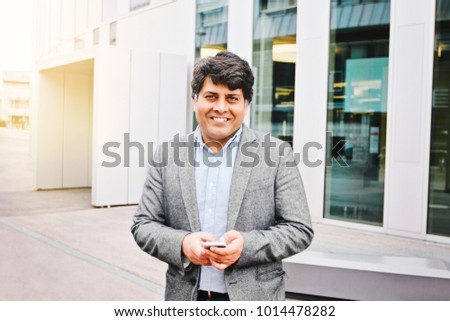 Middles aged indian businessman with smartphone, sunny day #1014478282