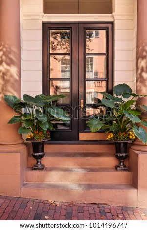 A secured entrance into a house in a posh urban area. The front door is brown and potted plants on on the steps. The exterior is made of brick. #1014496747