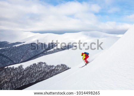 A man is skiing on the slope, wearing brigh  red yellow jumpsuit. Good skiing day, blue sky on the background. #1014498265