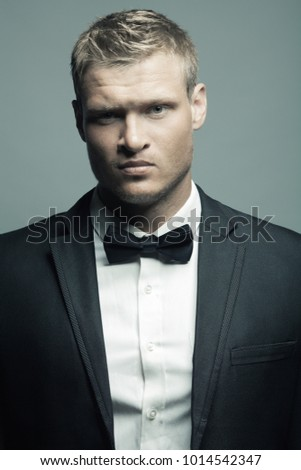 Male fashion, beauty concept. Portrait of brutal young man with short wet blond hair wearing black suit, posing over gray background. Classic style. Studio shot #1014542347