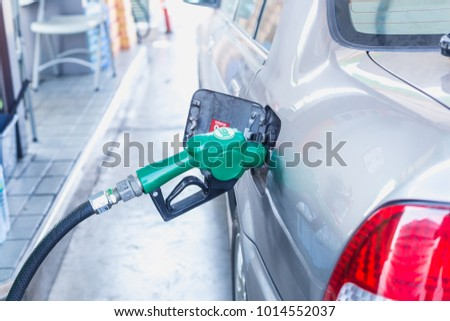 Grey car at gas station being filled with fuel on thailand #1014552037