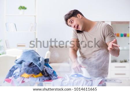 Inattentive husband burning clothing while ironing #1014611665