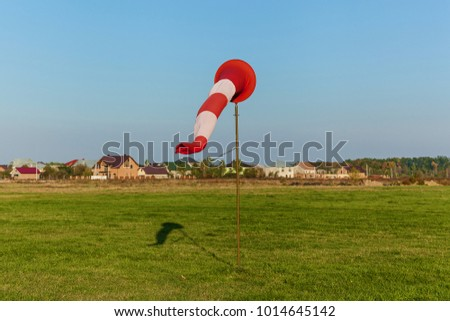 Cone on the runway on the background of grass and houses. Cone on the runway. #1014645142