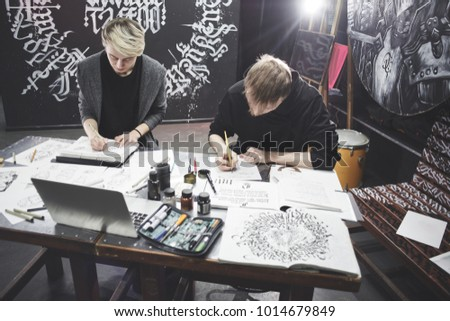 Portrait of the masters of calligraphy. Tattoo artists make a sketch sitting at the table in the Studio. This working process #1014679849