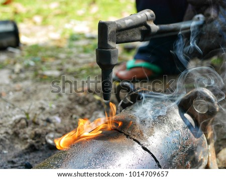 employees in the shop to buy gass spray gun.to cut the compressor is broken.to separate between copper and steel apart.to recycle Royalty-Free Stock Photo #1014709657