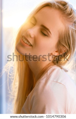 portrait of sensual young woman with closed eyes with sunset flare on background #1014790306