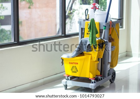 Cleaning cart with miscellaneous tools in corridor. #1014793027