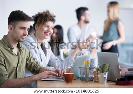 Satisfied businessman working with smiling businesswoman in the company #1014801625