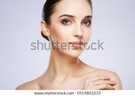 Cute girl with nude make up posing at grey studio background, beauty photo concept, looking at camera, perfect skin, close up. #1014803233