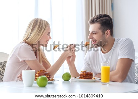 young couple feeding each other with breakfast #1014809410