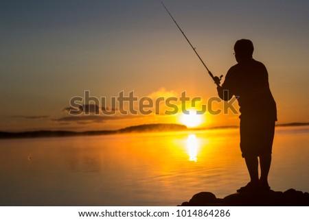 Siluette fishman at sunset at lake  #1014864286