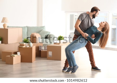 Young happy couple in room with moving boxes at new home #1014982612