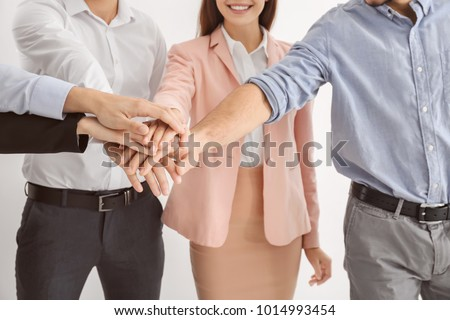 Young people putting hands together, closeup. Unity concept #1014993454