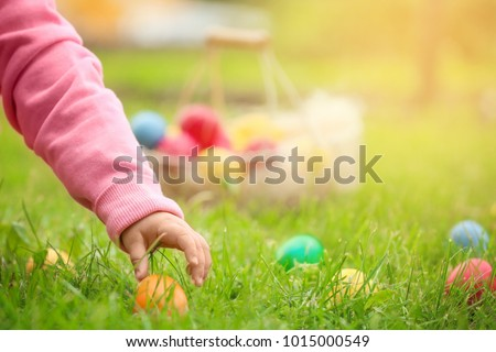Little girl gathering colorful egg in park. Easter hunt concept Royalty-Free Stock Photo #1015000549