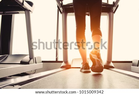 Lower body at legs part of Fitness girl running on running machine or treadmill in fitness gym with sun ray. Warm tone. Healthy and Exercise activity concept. Workout and  Strength training theme. #1015009342