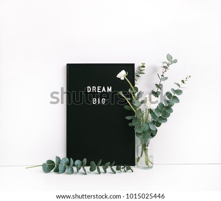 """Eucalyptus and ranunculus flower, letter board with motivational quote """"Dream big""""  on white table. Feminine home office. Minimal floral desktop with white wall."""