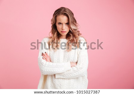 Picture of angry young woman standing isolated over pink background. Looking camera. Royalty-Free Stock Photo #1015027387