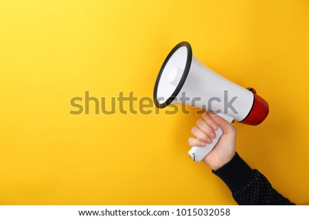 Woman holding megaphone on color background Royalty-Free Stock Photo #1015032058
