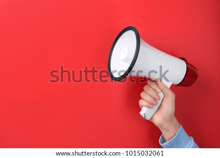 Woman holding megaphone on color background #1015032061