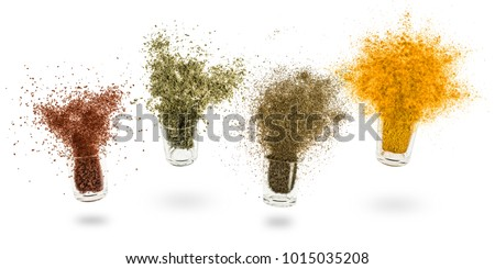 glass jars with various spices flying on white background Royalty-Free Stock Photo #1015035208