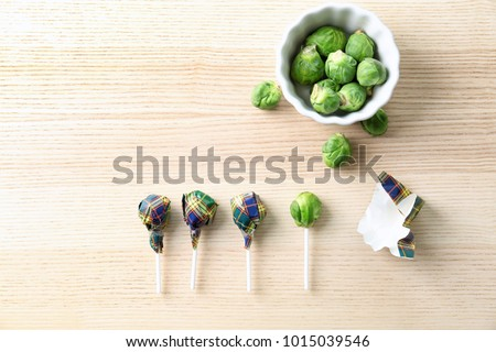 Brussel sprouts with lollipop sticks in candy wrappers on table. April fools food Royalty-Free Stock Photo #1015039546