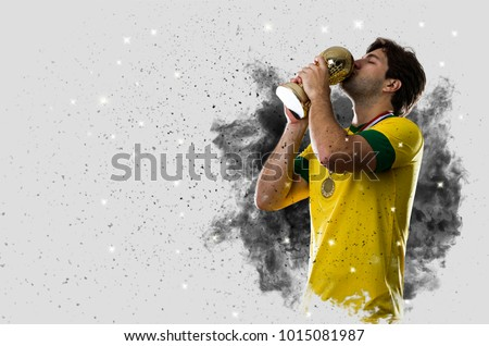 Brazilian soccer player coming out of a blast of smoke. celebrating with a trophy in his hand. #1015081987
