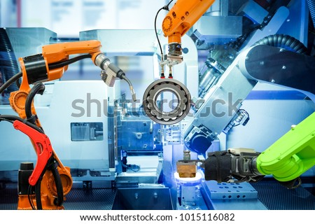Industrial robotic welding and robot gripping working on smart factory, on machine blue tone color background, industry 4.0 and technology. Royalty-Free Stock Photo #1015116082