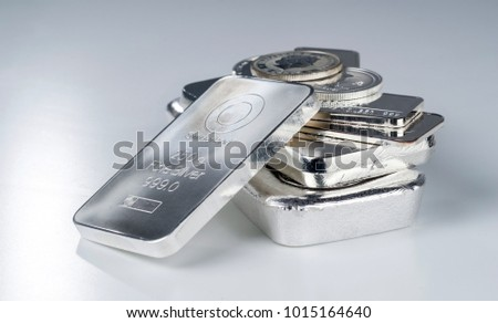 Silver bullion. Cast and minted bars and coins on a gray background. Selective focus. #1015164640