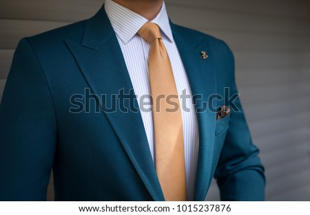 Man in elegant custom tailored expensive suit posing in front of background   #1015237876