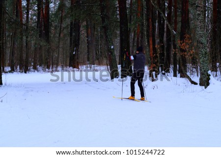 Skier in winter forest. A man is skiing in the winter forest. Rear view. #1015244722