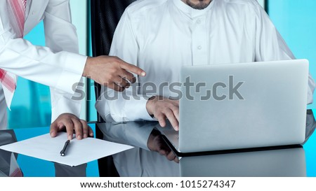 Arab Businessmen at Disk Working on a Laptop #1015274347