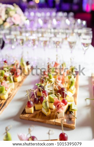 Furshet. Table top full of glasses of sparkling white wine with canapes and antipasti in the background. champagne bubbles #1015395079
