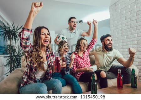 Happy friends or football fans watching soccer on tv and celebrating victory at home.Friendship, sports and entertainment concept. Royalty-Free Stock Photo #1015450198