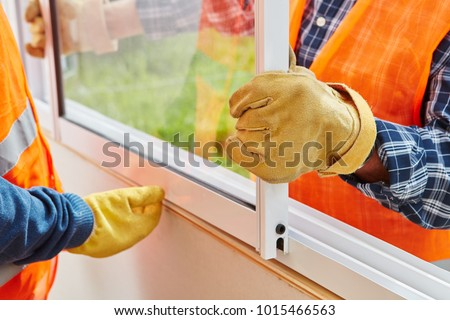 Window installation process made by two construction workers #1015466563