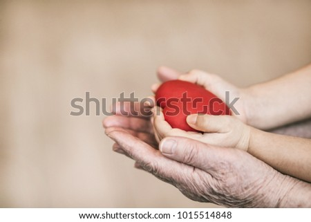 Red heart in child and grandmother hands. #1015514848