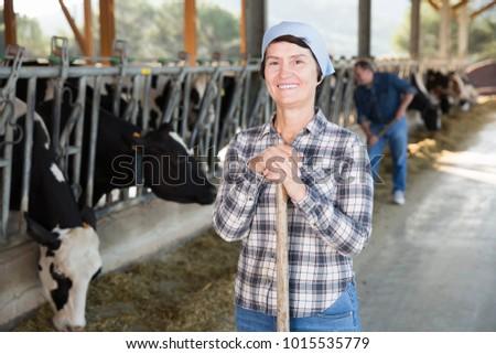 Confident female farmer posing on background of cows in stall #1015535779