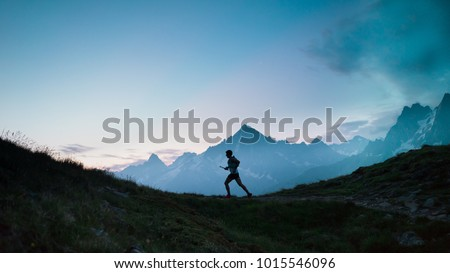 A single trail runner, silhouetted against the sky at sunrise while running in the mountains of the Alps along a steep trail #1015546096