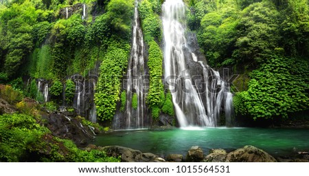 Jungle waterfall cascade in tropical rainforest with rock and turquoise blue pond. Its name Banyumala because its twin waterfall in mountain slope #1015564531