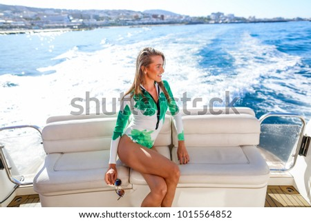 Girl in a swimwear rest on a yacht in the middle of the ocean  #1015564852
