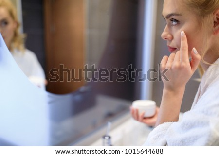 side view of attractive girl applying cream on face #1015644688