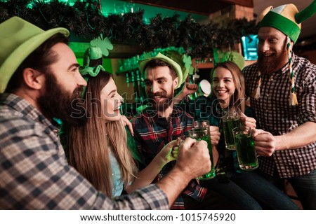 The company of young people celebrate St. Patrick's Day. They have fun at the bar. They are dressed in carnival headgear. #1015745920