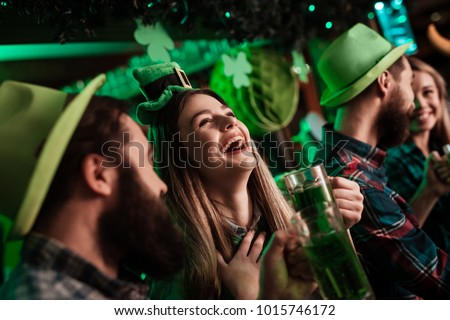 The company of young people celebrate St. Patrick's Day. They have fun at the bar. They are dressed in carnival headgear. #1015746172