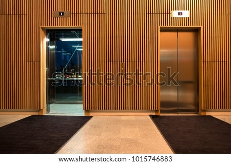 Detail of two modern elevators, with automatic steel doors, of a prestigious hotel. On the sides two wooden walls and on the bottom an elegant black carpet.   #1015746883