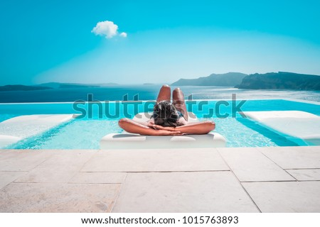 Young woman on vacation at Santorini, women at the swimming pool looking out over the Caldera ocean of Santorini, Girl at the infinity pool Oia Santorini Greece Royalty-Free Stock Photo #1015763893