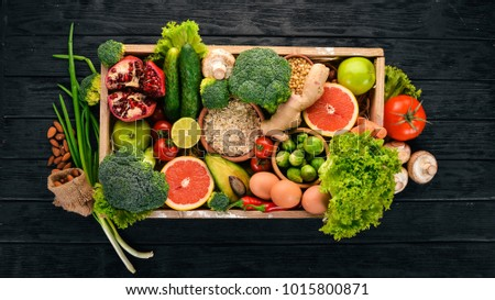 The concept of healthy food. Fresh vegetables, nuts and fruits in a wooden box. On a wooden background. Top view. Copy space. #1015800871