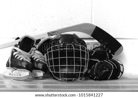 Black and white photo of kid's hockey accessories: helmet, hockey stick, gloves, skates on brick background.