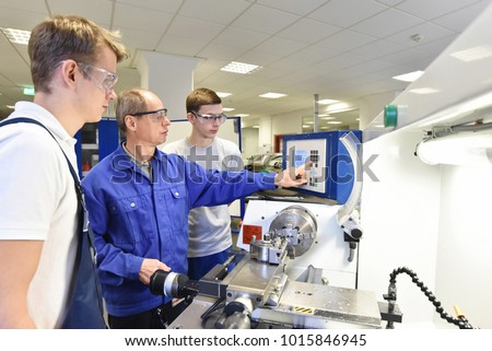 young apprentices in technical vocational training are taught by older trainers on a cnc lathes machine Royalty-Free Stock Photo #1015846945